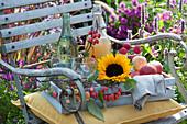Holzkiste mit Sonnenblume, Äpfeln, Zieräpfeln, Flaschen mit Apfelsaft und Wasser, Gläser