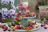 Selbstgebaute Etagere aus Haushaltsutensilien herbstlich dekoriert mit Äpfeln, Zieräpfeln, Hagebutten, Kastanien, Strohblumen und Hortensienblüten