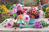Kleine Sträuße aus Rosen, Hagebutten und Herbstastern