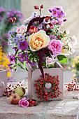 Herbststrauß aus Rosen, Astern, Hagebutten und Amaranth in alte Holzschublade gestellt, Kränzchen aus Hagebutten