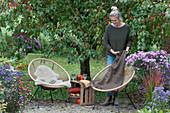 Kleine Sitzgruppe vor Zierapfelbaum, Frau legt Decke auf Sessel
