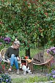 Kleine Sitzgruppe mit Frau und Hund Zula vor Zierapfelbaum