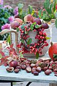 Zierapfel-Kränzchen an Korb mit frisch gepflückten Äpfeln, Kastanien, Kürbis und wilder Wein als Deko