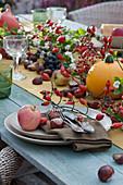 Herbstliche Tischdeko mit Hagebutten, Kürbis, Apfel, Kastanien, Schneebeeren