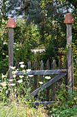 Hölzernes Gartentor mit Tontöpfen auf den Torpfosten