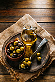 Glass jar with extra virgin oil placed on wooden plate with black and green olives