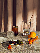 Mixing glass and stirring spoon, orange and olives