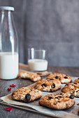 Yummy crunchy freshly baked oatmeal cookies on baking paper placed on table near bottle and glass with milk during breakfast