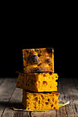 Pieces of freshly baked Focaccia bread with curcuma placed on wooden table on black background