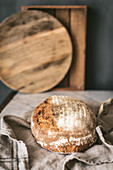 Round loaf of delicious homemade bread placed on piece of cloth on table in kitchen