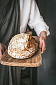 Unrecognizable baker in apron with loaf of tasty bread placed