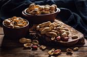 Erdnüsse in Schalen und auf Holzbrett