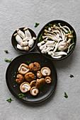 Verschiedene rohe Pilze mit frischer Petersilie auf schwarzen Tellern