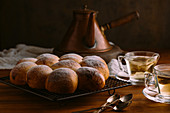 Identical appetizing buns with round shape and golden surface decorated with sugar powder on metal cooling rack on wooden table