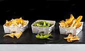 Mexikanische Snacks: Nachos, Edamame und Kochbananenchips in Papierschalen