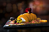 Snack of mango cannelloni filled with cream cheese and garnished with tender flowers
