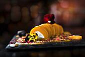 Mango-Cannelloni mit Frischkäsefüllung, garniert mit Blüten