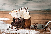 Chocolate cake with meringue placed on wooden table against shabby background