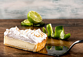 Slice of lemon pie with piped and toasted meringue on table with lime