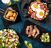 Spanish food including croquettes and tuna salad and Iberian pork and fried eggs with ham served on table