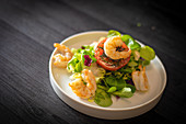 Healthy spinach salad with shrimps and tomato served on withe ceramic plate on black table