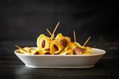 Würstchen in Kartoffelchips eingewickelt, mit Zahnstochern