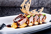 Tuna pieces with garnished with caviar and unagi sauce served on white plate