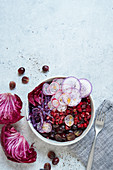 Purple bowl with marinated beetroot, red cabbage, grapes and pomegranate