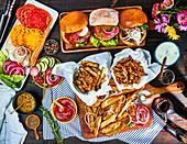 Verschiedene Burger mit Pommes Frites und Zutaten
