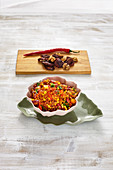 Chili con carne with minced nuts, corn and carrots