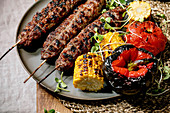 Grilled spicy beef lyulya kebab on sticks on flat bread with grilled vegetables sweet corn cob, tomato and paprika