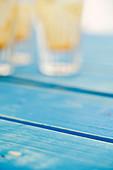 Blauer Holzuntergrund, leer getrunkene Gläser im Hintergrund
