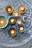 Small bowls with red lentils and tea lights as decorations