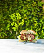 Ein Burger mit Käsefüllung auf Tisch im Freien