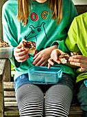 Kinder essen Blechkuchen aus Lunch-Boxen
