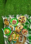 Picknick mit pikanten und süssen Gerichten auf Picknickdecke