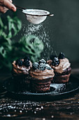 Chocolate cupcakes with coffee cream and blackberries sprinkled with powdered sugar