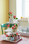 DIY-Etagere dekoriert mit Rosenblüten in kleinen Vasen