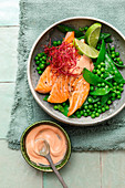 Bowl with sugar snap peas and pea salad and salmon