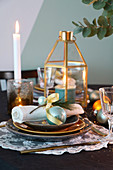 Dining table festively set in gold and turquoise