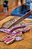 Seared tuna steak being cut into strips