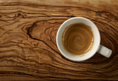 Freshly brewed espresso on an olive wood surface