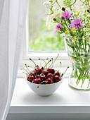 A bowl of cherries on a windowsill