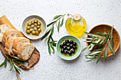 Green and black olives with olive oil in a glass bottle, olive tree sprigs and cut fresh ciabatta bread
