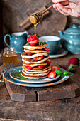 Pancakes with strawberries and honey dripping
