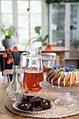 Gugelhupf mit Zuckerguss und Blüten, Schokolade und Getränk auf Tisch