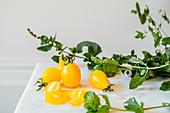 Gelbe Tomaten und frische Minze auf Marmorplatte