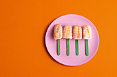 Top view of palatable set of Ebi Nigiri sushi with prawns served in shape of popsicle and placed on plate on orange background in studio