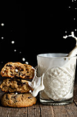 Pile of tasty chocolate cookies placed on wooden table near glass with splashing milk