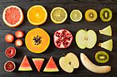 Verschiedene geschälte und geschnittene Obstsorten auf Holztisch
